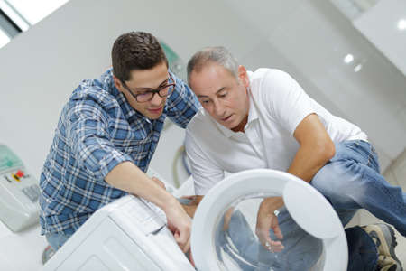 trainee and mentor fixing a washing machine