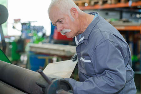 Alter Mechaniker arbeitet in einer Fabrik Standard-Bild - 90453531