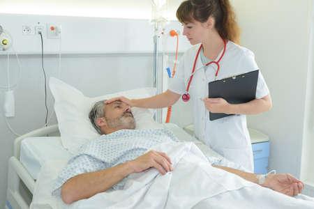nurse holding sicks man forehead