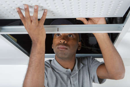 man installs suspended ceiling in house Stock fotó