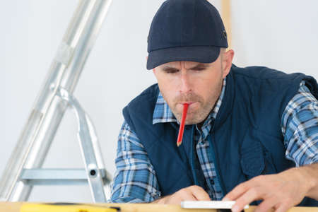 Tradesman working with pencil in his mouth Фото со стока