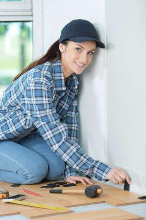 femme en train d'installer un sol stratifié