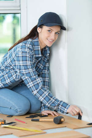 woman installing laminated flooring Stock Photo
