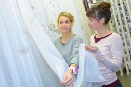 two women choosing curtain in supermarket