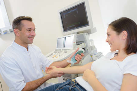 male doctor with female patient undergoing arm echography