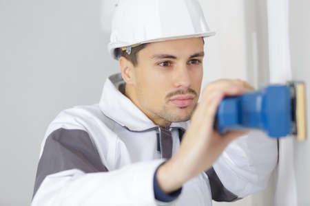 male builder sanding wall indoors