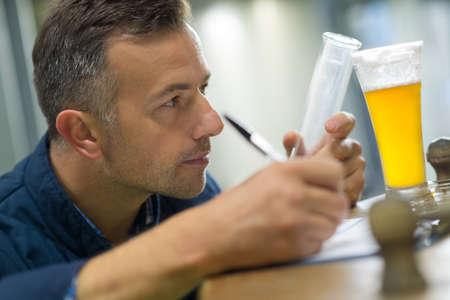 attentive brewer testing beer at brewery Standard-Bild