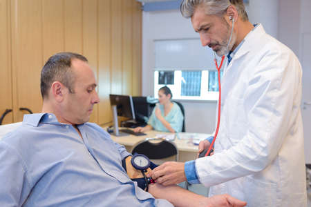 doctor checking mature male patient blood pressure