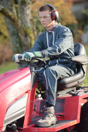 young gardener on ride-on lawn mower cutting grass