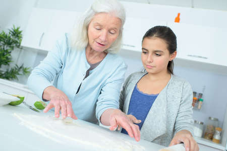 young girl making a cake with her nanny Stock Photo