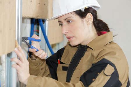 tradeswoman on site using pliers