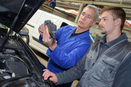 auto mechanic teacher and trainee performing tests at mechanic school Stock Photo