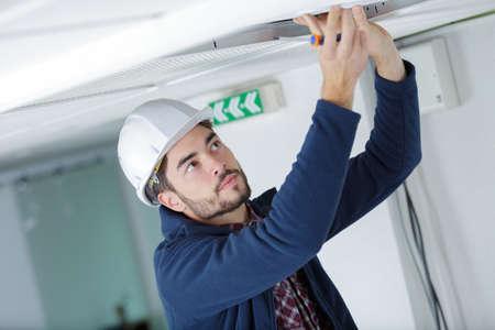 elettricista maschio con cacciavite riparazione sensore antincendio
