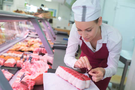 female butcher tying joint of meat