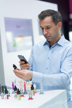 man taking a picture of vape refill Stock Photo