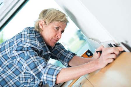 woman laying laminate flooring at home Stock Photo