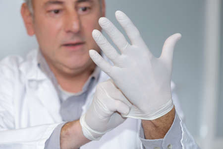 doctor puts a glove on his hand Stock Photo