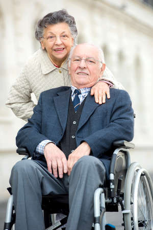 senior man being pushed by wife in wheelchair Stock Photo
