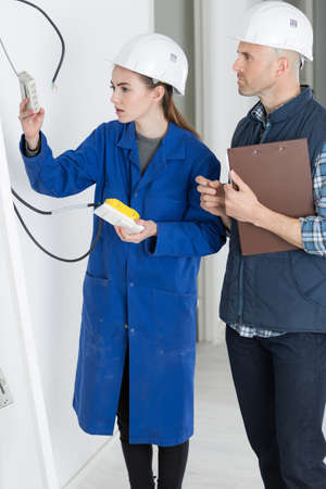 young female trades apprentice wiring a socket