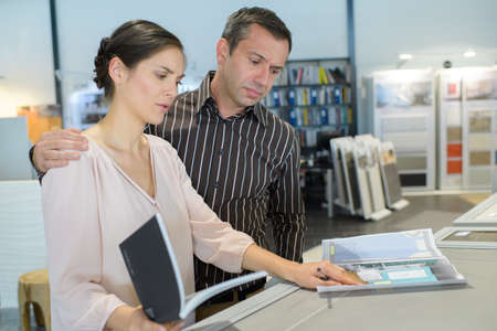 couple looking at a catalogue in a store Banco de Imagens