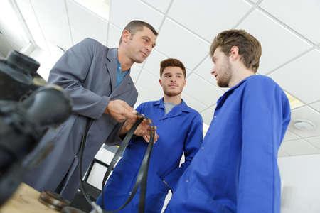 apprentice mechanics in auto shop working on car engine Foto de archivo