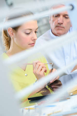 dental technician painting tooth at prosthesis laboratory Stock Photo