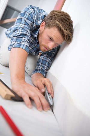 young handyman fitting carpet while installation with cutter