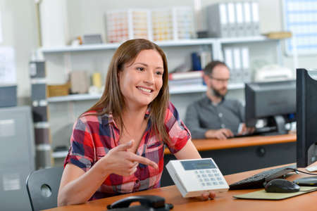 Lady sat at desk showing display on calculator