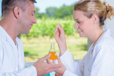 Man and woman holding glass flask in laboratory