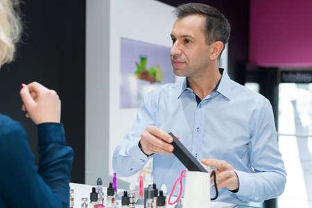 male seller advising client in vape store