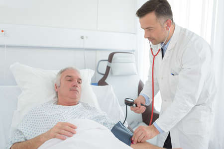 trained medical worker checking patients pressure