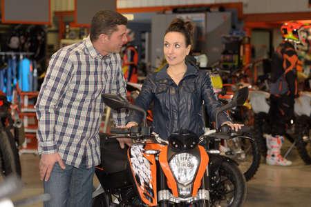 pretty seller with interested male customer near motorbike Фото со стока
