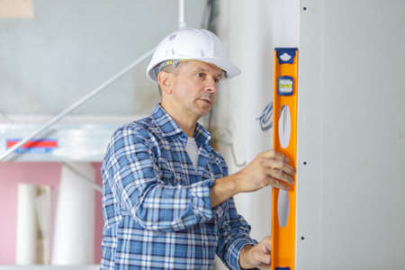 professional builder with spirit level at construction site Stockfoto