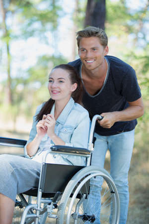 peaceful young couple in wheelchairs in park