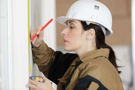 low angle shot of female carpenter working with spirit level Stockfoto