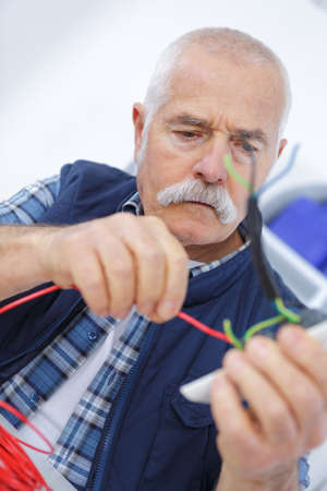 senior worker plugging socket type to electrical outlet Stock Photo