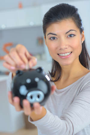 female hand putting coin into piggy bank closeup Banque d'images