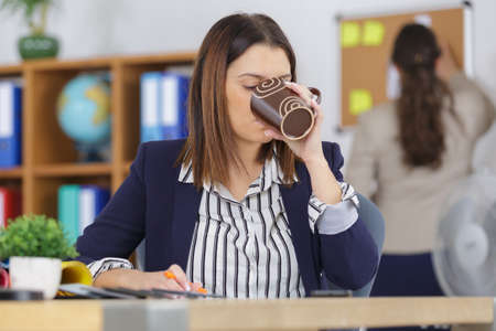 beautiful woman drinking coffee in a office