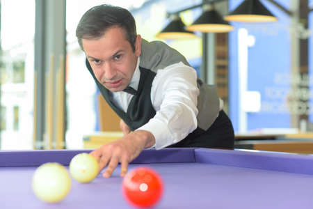 man playing billiard in a pool hall