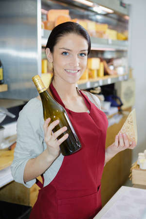 woman presenting a selection of different cheeses and wine