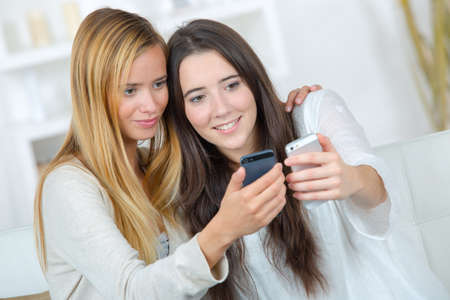 two casual girls watching on line promotions on a cellular Stock fotó