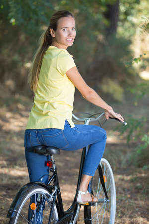 woman cycling in a forest in the countryside