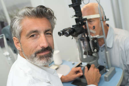 happy optometrist doing sight testing to senior patient