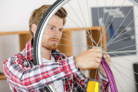 man fixing wheel on a bicycle Banque d'images