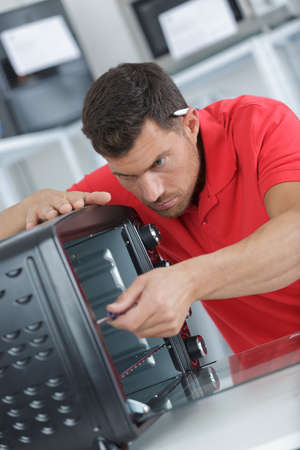 young male technician repairing oven in kitchen Banque d'images