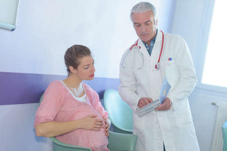 pregnant patient talking to doctor with notes in medical office