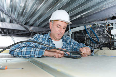 electrician holding cable in wiring ceiling