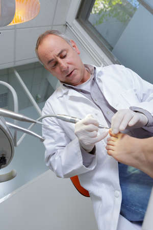 mature podologist curing patients foot Stock Photo