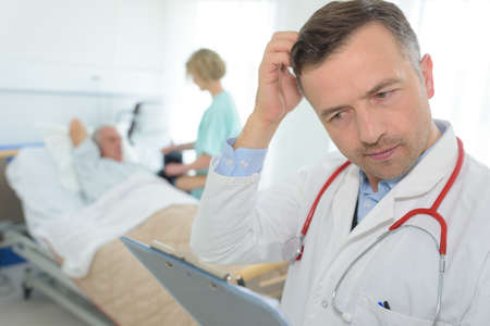 frustrated mature doctor scratching his head in patients room Stock Photo
