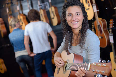 woman holding a guitar in the guitar store Stock Photo